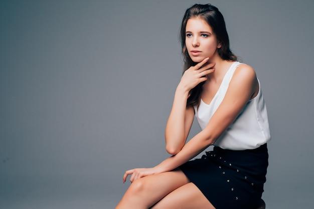 Garota séria sentar em uma cadeira alta de madeira em estúdio isolado no fundo branco