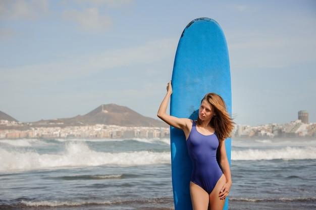 Garota sexy com maiô azul em pé com a prancha de surfe sobre o oceano atlântico