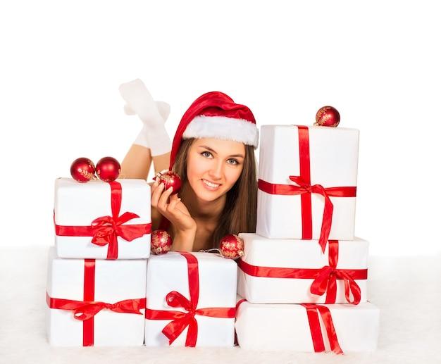 Garota sexy com presentes de natal deitada no tapete, sorrindo e olhando para a câmera