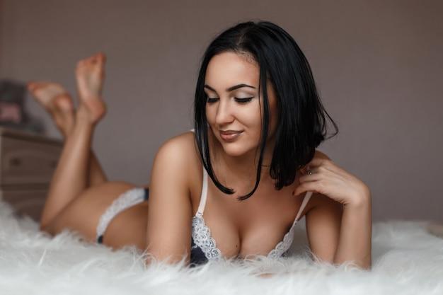 Garota sexy com um lindo corpo bronzeado na cama