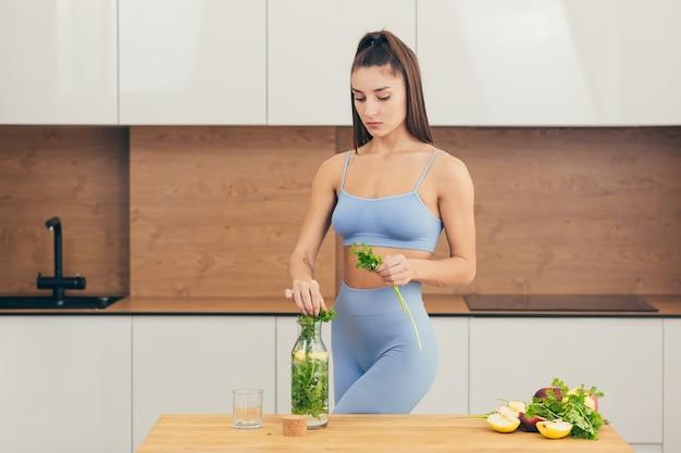 Garota sexy, desportista prepara em casa uma bebida fresca de frutas e verduras