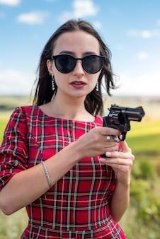 Garota sexy e esguia em um vestido vermelho segurando uma arma para a natureza, estilo de vida de verão