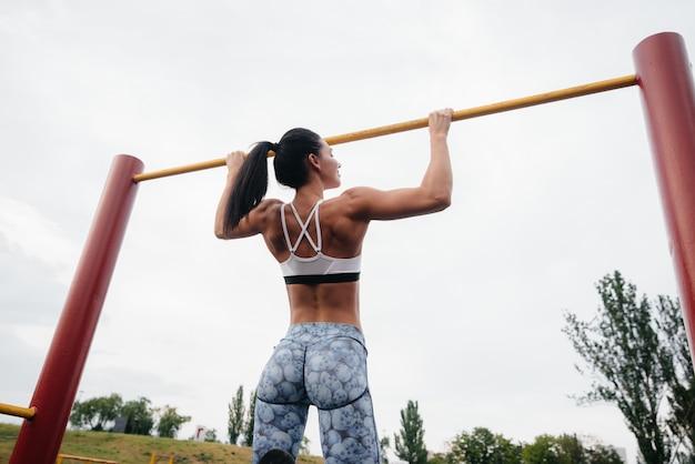 Garota sexy é puxada para cima em uma barra horizontal ao ar livre. ginástica. estilo de vida saudável