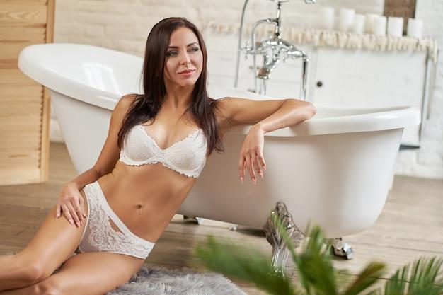 Garota sexy em cueca posando no banheiro perto da banheira branca