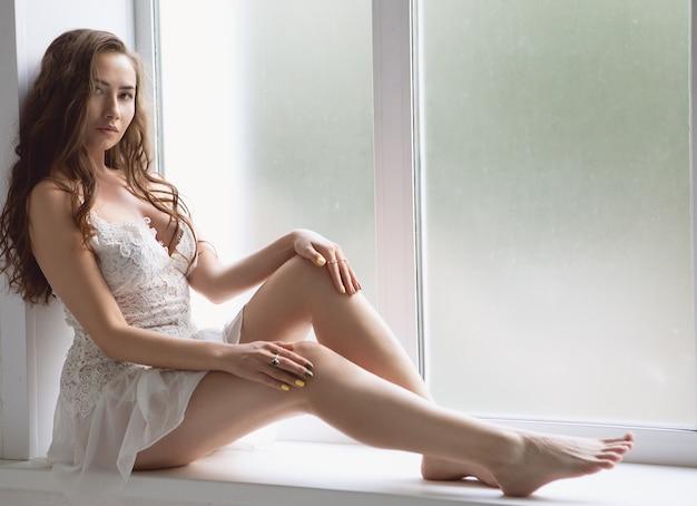 Garota sexy em lingerie branca, sentada no peitoril da janela de uma grande janela