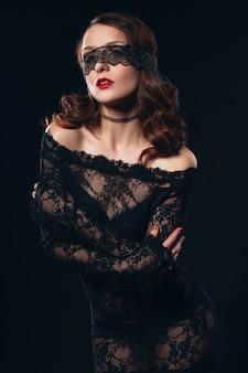 Garota sexy em lingerie preta máscara em preto