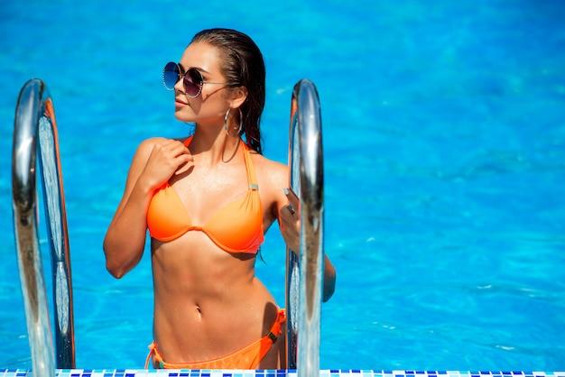Garota sexy em maiô da moda e óculos escuros na piscina