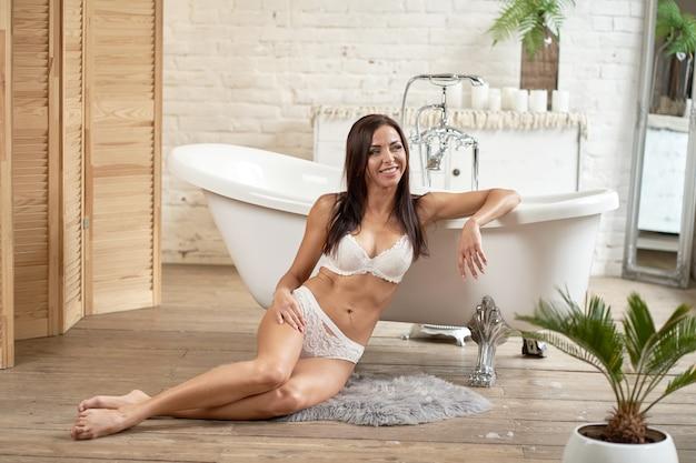 Garota sexy em roupa interior posando no banheiro perto do banho branco.