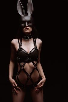 Garota sexy em roupa íntima e arreios de couro e máscara. conceito de bdsm
