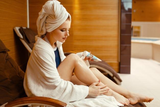 Garota sexy em roupão de banho e toalha na cabeça aplicando creme na cadeira do spa