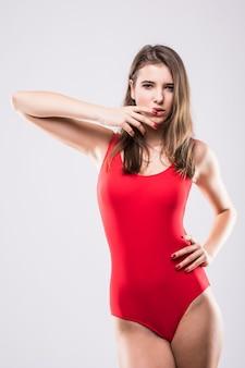 Garota sexy em suíte de natação vermelha isolada no fundo branco