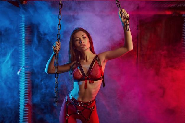 Garota sexy em um terno bdsm vermelho segurando correntes, abandonou o interior da fábrica. jovem em roupa íntima erótica, fetiche sexual, fantasia sexual