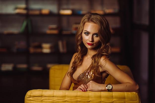 Garota sexy em um vestido de ouro sobre o fundo de livros na biblioteca. modelo com cabelo comprido e batom vermelho no interior.