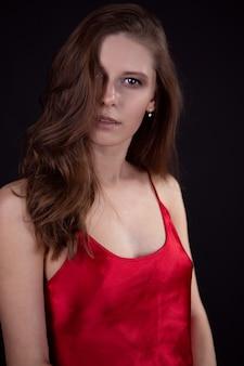Garota sexy em uma camisola vermelha com uma bela maquiagem e cabelo em uma parede preta