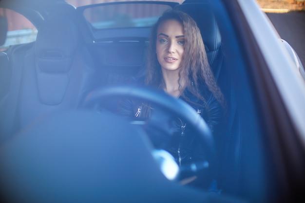 Garota sexy em uma jaqueta de couro, shorts jeans e meia-calça preta na net senta-se ao volante de um carro