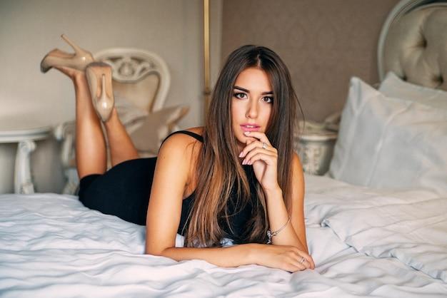 Garota sexy encantadora e atraente de vestido preto elegante, deitada em uma cama em um quarto de hotel