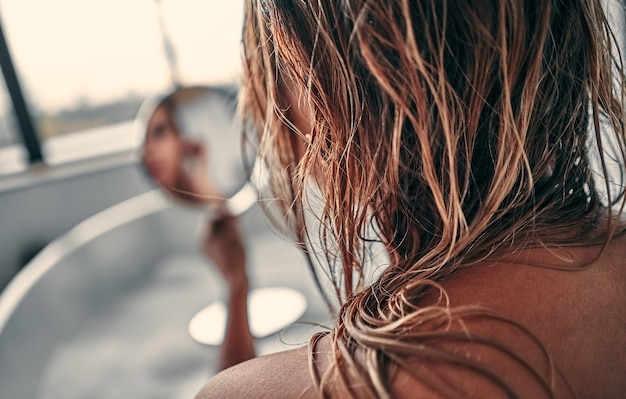 Garota sexy encontra-se relaxa em uma banheira com espuma, olha-se em um espelho redondo, vista traseira.