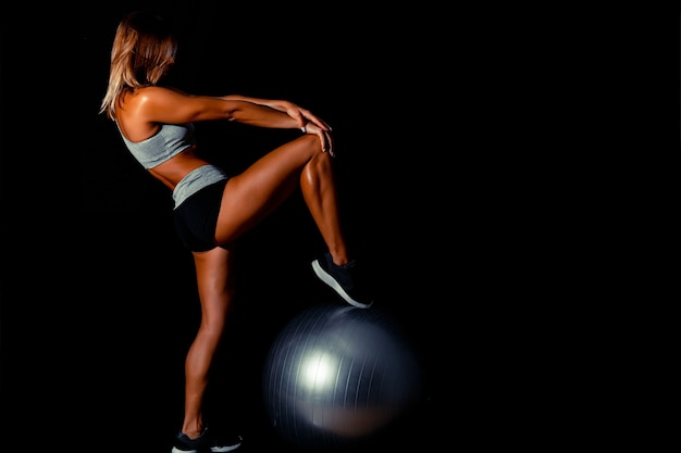 Garota sexy esporte escuro em roupas esportivas realiza flexões em fitball cinza no ginásio.