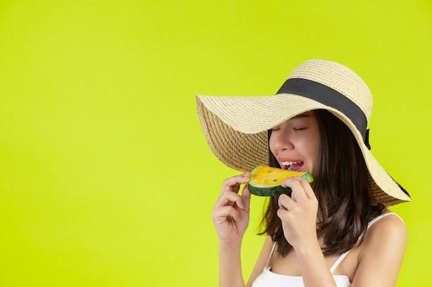 Garota sexy está comendo melancia em sumer tempo quente com chapéu na parede amarela.