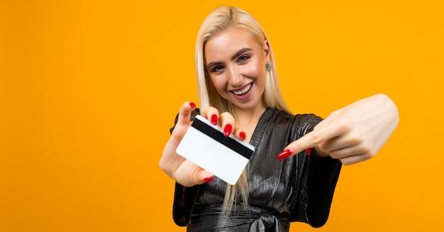 Garota sexy europeia tem um cartão de crédito com uma maquete para fazer compras em um amarelo.