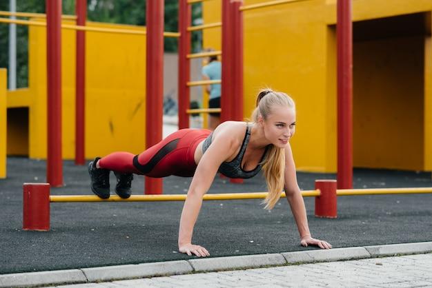 Garota sexy fazendo push-ups ao ar livre. ginástica. estilo de vida saudável