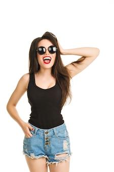 Garota sexy glamour da moda com lindo sorriso branco como a neve, diversão enlouquecendo de descanso, chora. menina morena elegante em jeans e roupa hippie. fundo branco isolado. moda óculos redondos lábios vermelhos