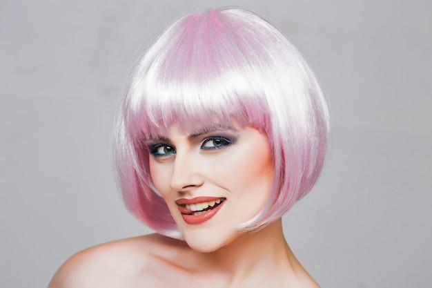 Garota sexy glamour ou mulher com maquiagem da moda em um rosto muito sorridente e penteado curto ou peruca rosa