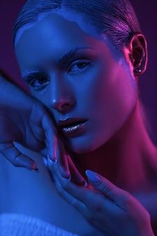 Garota sexy jovem em luzes azuis de néon com glitter roxo.