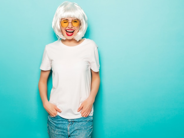 Garota sexy jovem sorridente hipster de peruca branca e lábios vermelhos. mulher bonita na moda em roupas de verão. modelo despreocupado posando perto de parede azul no verão de estúdio enlouquecendo
