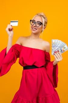 Garota sexy loira em um vestido vermelho com ombros nus detém um monte de dinheiro do empréstimo e uma maquete de crédito de cartão de crédito em um espaço isolado do estúdio