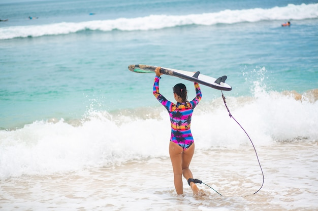 Garota sexy magro com prancha de surf na praia de areia tropical. estilo de vida ativo e saudável na vocação de verão.