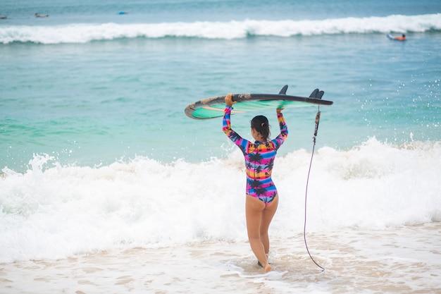 Garota sexy magro com prancha de surf na praia de areia tropical.