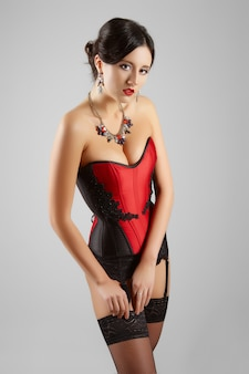 Garota sexy no espartilho burlesco e lingerie posando contra a parede