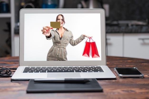 Garota sexy, posando com um cartão de desconto e bolsas vermelhas. conceito de compras na sexta-feira negra. fundo branco. mídia mista