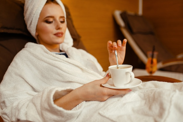 Garota sexy relaxando com uma xícara de café na cadeira do spa