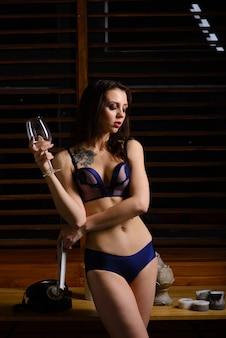 Garota sexy sensual em lingerie azul e sapatos de salto alto pretos em um interior claro.