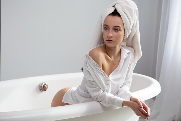 Garota sexy sentada no banheiro com uma toalha na cabeça
