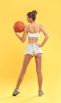 Garota sexy vestindo shorts curtos, segurando uma bola de basquete na parede amarela