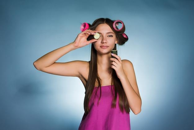 Garota simpática quer ser linda, na cabeça grandes rolinhos, segura um pepino para hidratar a pele do rosto