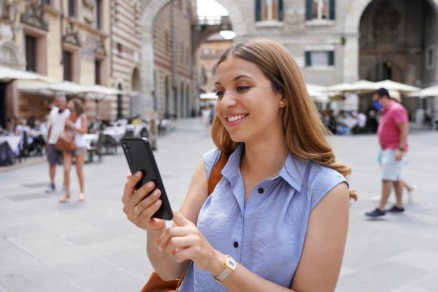 Garota simpática, rolando em seu telefone móvel ao ar livre. mulher atraente e elegante sorridente digitando no smartphone na praça de verona, itália.