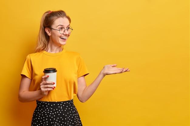 Garota sincera e positiva bebe café aromático em copo descartável mantendo a mão levantada