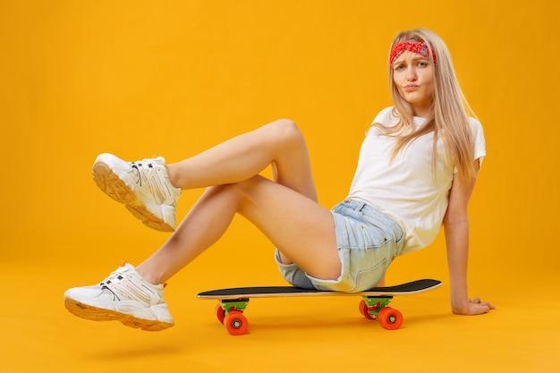 Garota skatista de bermuda e camiseta, sentado a bordo sobre fundo amarelo