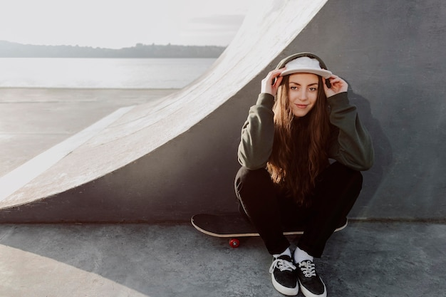 Garota skatista de frente para o lado da rampa
