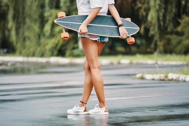 Garota skatista em pé cruzado as pernas segurando seu longboard