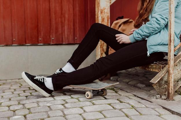Garota skatista na cidade, sentada na escada, vista lateral
