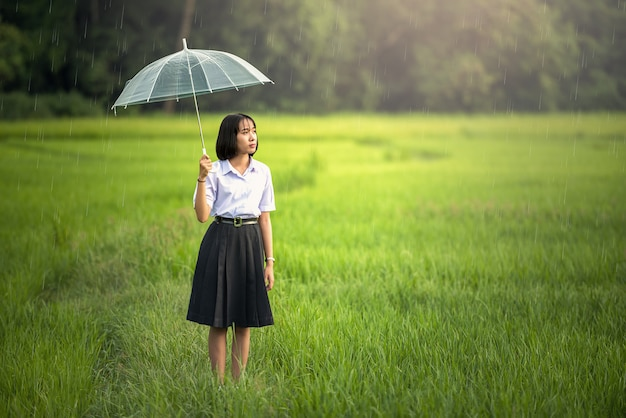 Garota sob um guarda-chuva na chuva