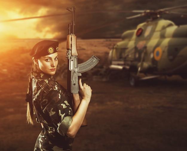 Garota soldado em uniforme militar está perto de um helicóptero no campo de batalha