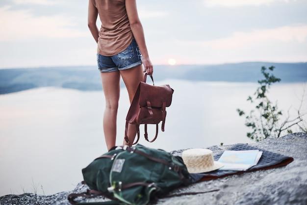 Garota solitária em pé perto da borda da rocha, observando a bela paisagem com a bolsa nas mãos.