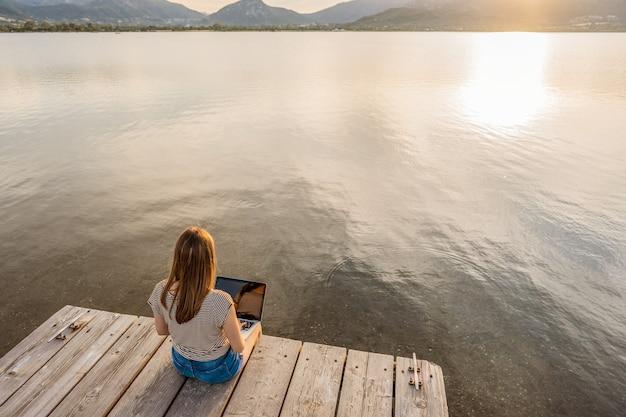Garota solitária expressando sua criatividade escrevendo um livro de contos de romance em um píer de madeira ao pôr do sol