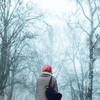 Garota solitária no parque enevoado